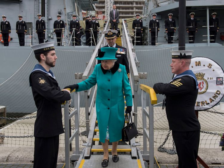 Queen walking down the plank of HMS Sutherland during visit to hear Hurricane irma rescue stories.