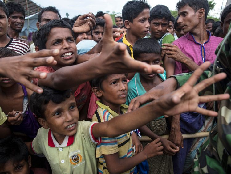 Rohingya boys reach for humanitarian aid as the Bangladesh military keeps things under control