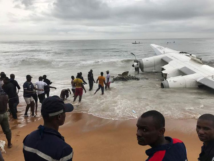 People pull items from the sea after a military-chartered plane crashes in Ivory Coast