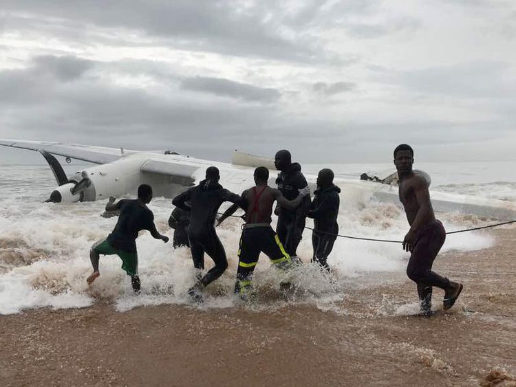 People help with a recovery operation to pull a down plane from the ocean in Ivory Coast