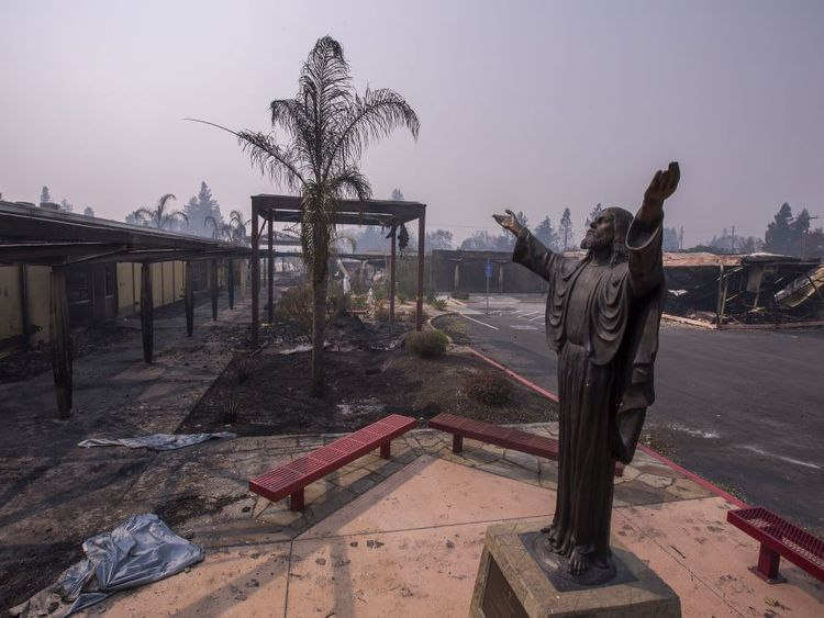 A statue of Jesus among fire damaged buildings at a school in Santa Rosa