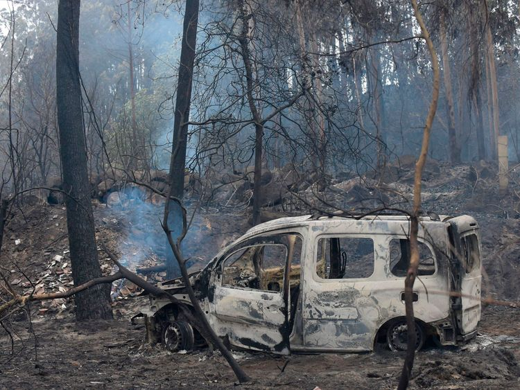 The wreckage of a burned van where two people died trapped by flames in Chandebrito, northwestern Spain