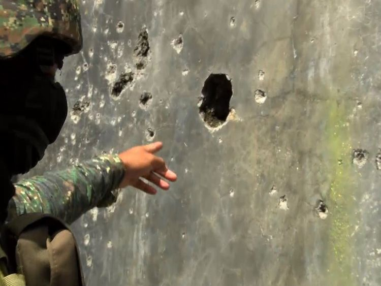 A soldier points out a hole used by militants to fire through