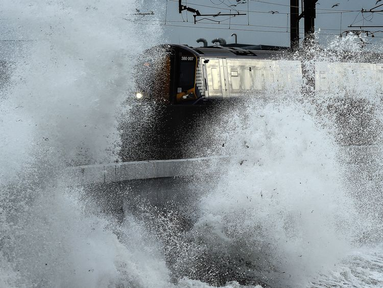Waves crash over railway tracks in Saltcoats on the west coast of Scotland