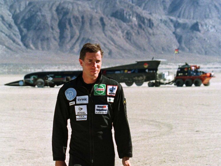 Andy Green, driver of ThrustSSC, the British jet car in the background that will attempt to break the world land speed record and possibly the sound barrier, walks away from ThrustSSC in 1997