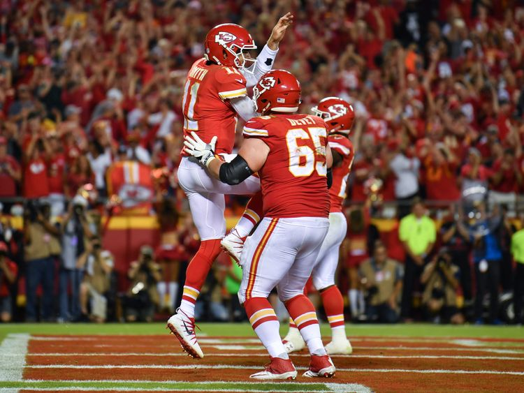 KANSAS CITY, MO - OCTOBER 2: Quarterback Alex Smith #11 of the Kansas City Chiefs leaps towards teammate Jordan Devey after a one yard touchdown run in the