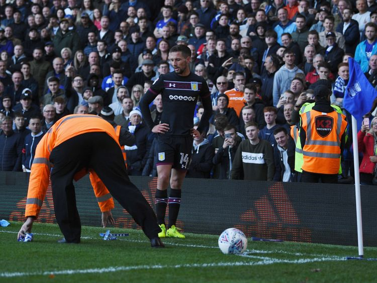 Clappers are removed from the pitch as Conor Hourihane of Aston Villa prepares to take a corner