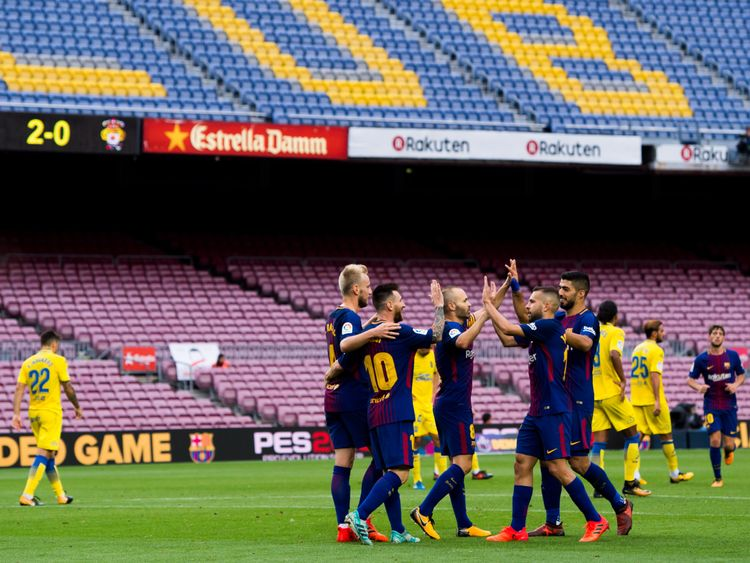 Lionel Messi celebrates with team-mates inside an empty Nou Camp stadium during the behind closed doors La Liga match against Las Palmas