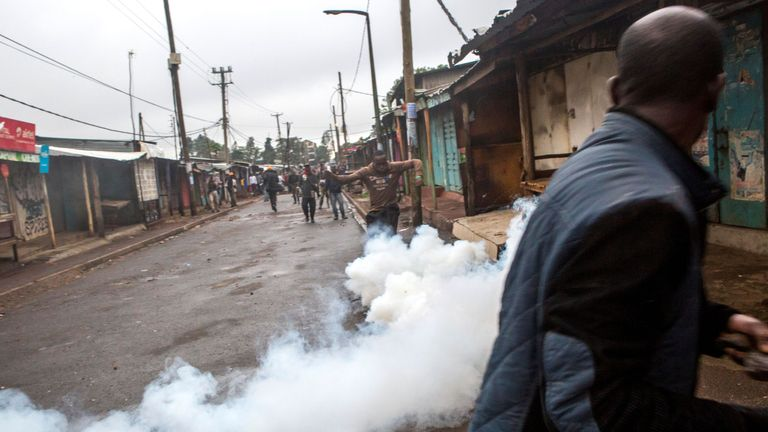 Residents react as tear gas fills a street in Kibera in Nairobi