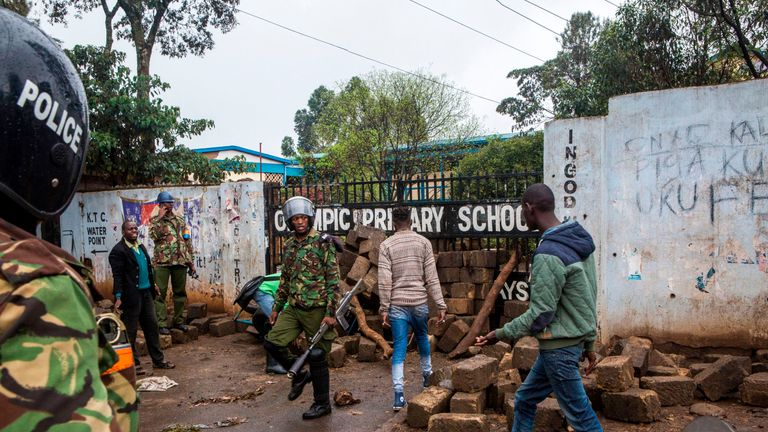 Opposition supporters clash with police after blocking a polling station at a school in Kibera, Nairobi
