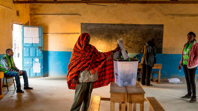 A member of the Maasai and Kikuyu tribe votes at a polling station at a school in Masailand