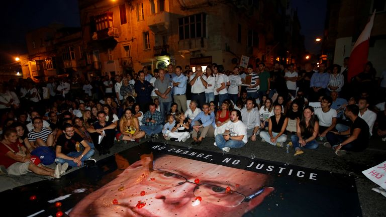 Protesters throw tomatoes and coins on a banner calling on Malta Police Commissioner Lawrence Cutajar to resign