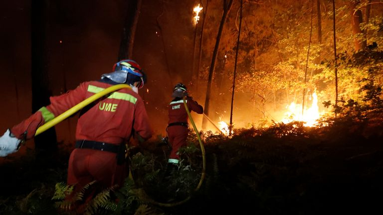 Firefighters from the Military Emergency Unit (UME) work to put out a forest fire near As Nieves, northern Spain, October 15, 2017