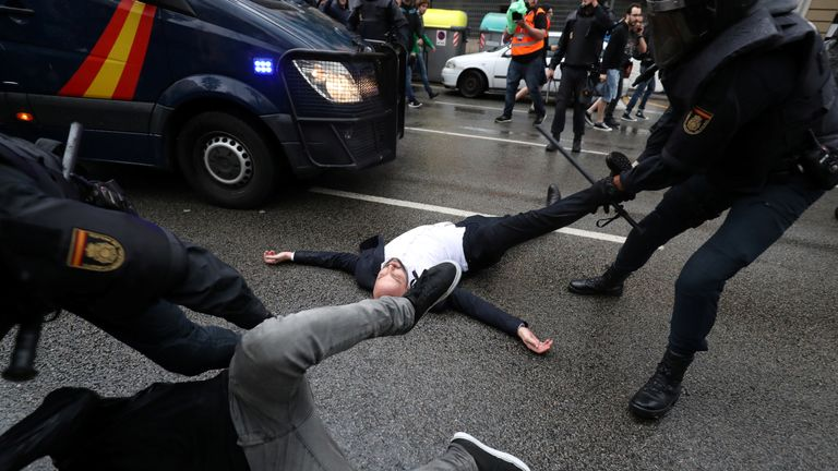 Protesters are dragged from the road by police in Barcelona