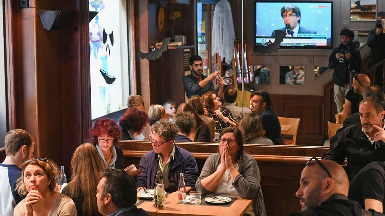 Customers in a Barcelona bar watch Carles Puigdemont's speech on TV