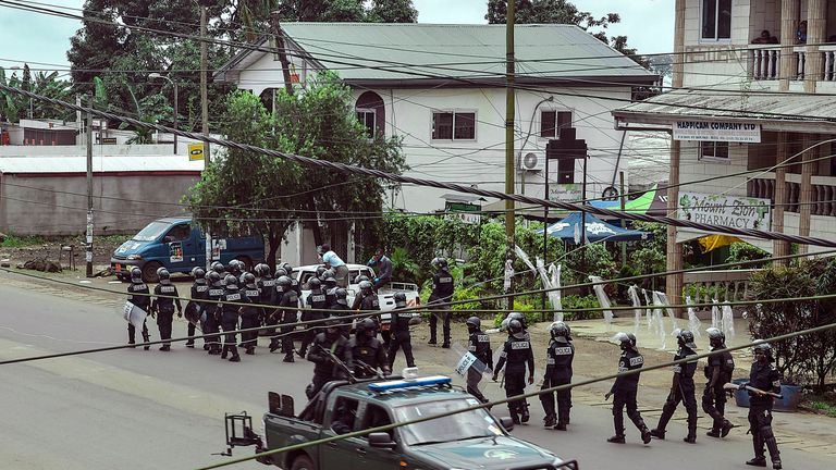 Cameroon police officials with riot equipment patrol along a street in the administrative quarter of Buea