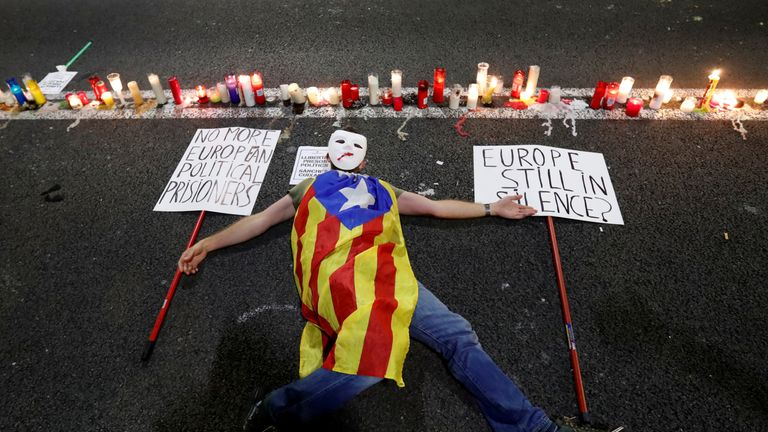 A man with a Catalan separatist flag lies on the ground during a protest in Barcelona