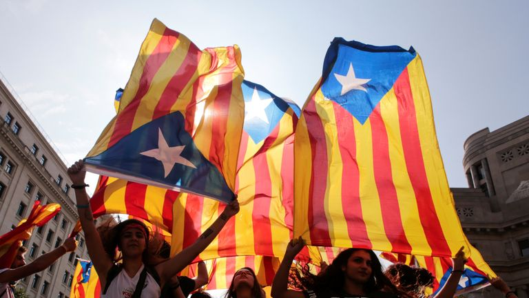 People hold Catalan flags during protests over the referendum in Barcelona