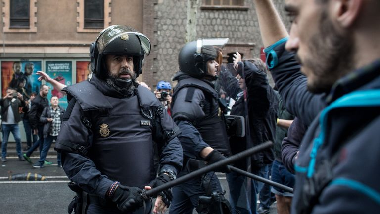 Police face off with protesters outside the polling station at Barcelona's industrial school