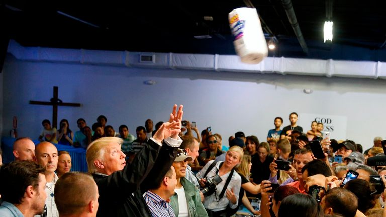 Donald Trump throws rolls of paper towels into a crowd of people affected by Hurricane Maria