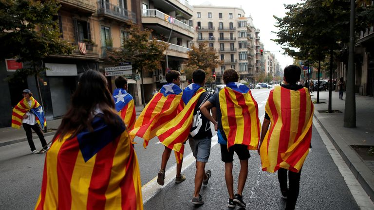 People wrapped in Esteladas (Catalan separatist flags) walk through a street during a protest two days after the banned independence referendum in Barcelona, Spain, October 3, 2017. Picture taken October 3, 2017