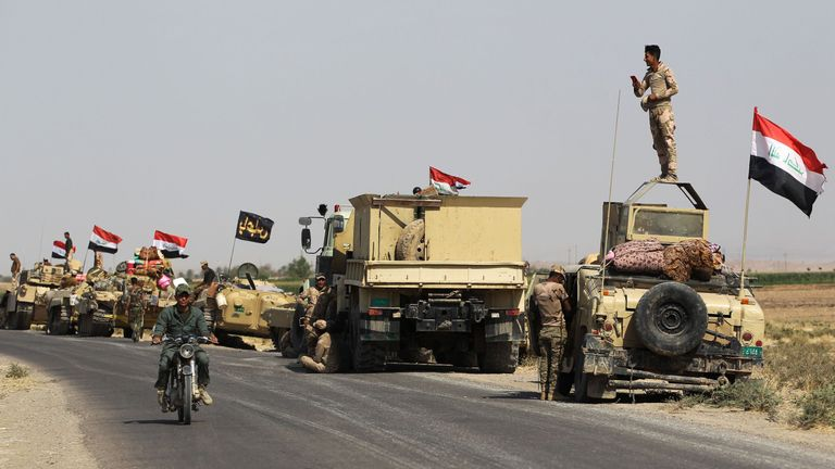 Iraqi forces rest on the road as they drive towards Kurdish peshmerga positions on October 15, 2017, on the southern outskirts of Kirkuk