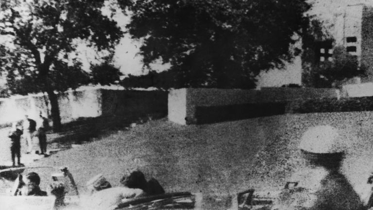 John F. Kennedy (1917 - 1963) is struck by an assassin's bullet as he travels through Dallas