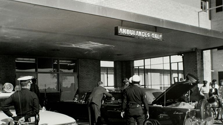 Secret Service agents and local police examine the presidential limousine as it sits parked at Parkland Memorial Hospital in Dallas