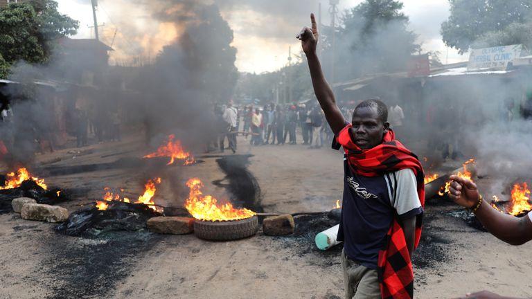 KENYA-ELECTION/RTX3I5GJ25 Oct. 2017Nairobi, KenyaAn opposition supporter gestures in front of a burned barricade in Kibera slum in Nairobi, Kenya October 25, 2017. REUTERS/Goran Tomasevi
