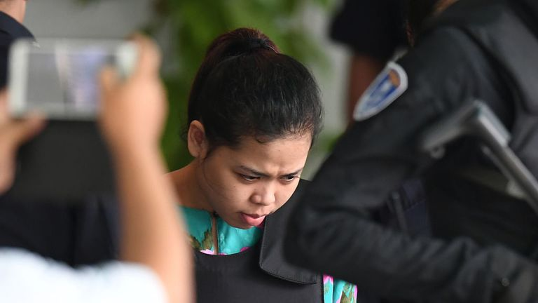Siti Aisyah is escorted by police after her appearance at the chemistry lab