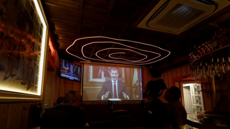 Patrons at a bar in Spain watch as King Felipe makes a televised address to the nation