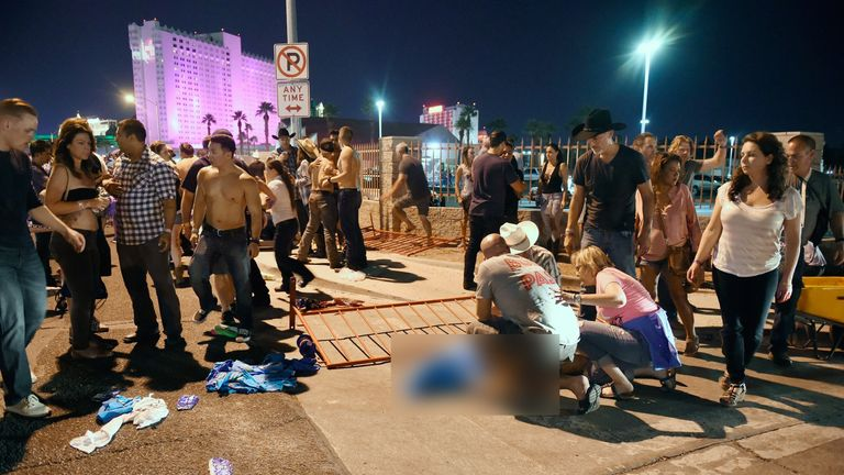 People tend to the wounded outside the Route 91 Harvest Country music festival grounds