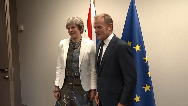 Theresa May posing with Donald Tusk in front of Britain and Europe flag.