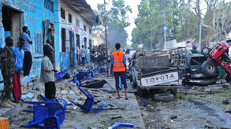 People standing at the scene of a blast after two car bombs exploded in Mogadishu on 28 October 2017