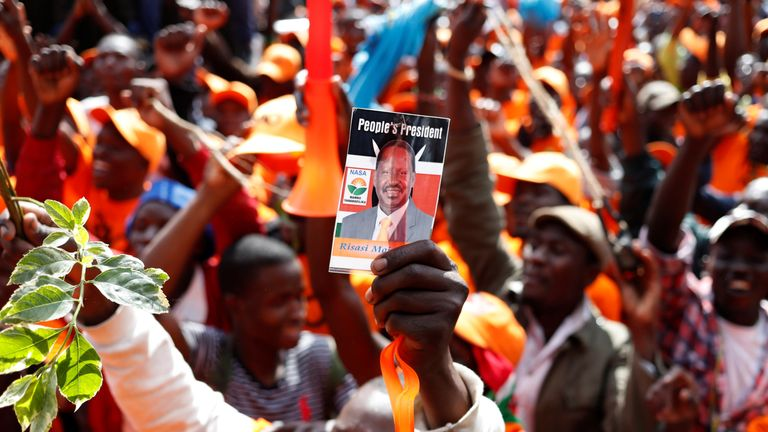 An opposition supporter holds up a picture of opposition leader Raila Odinga during a rally in Nairobi..