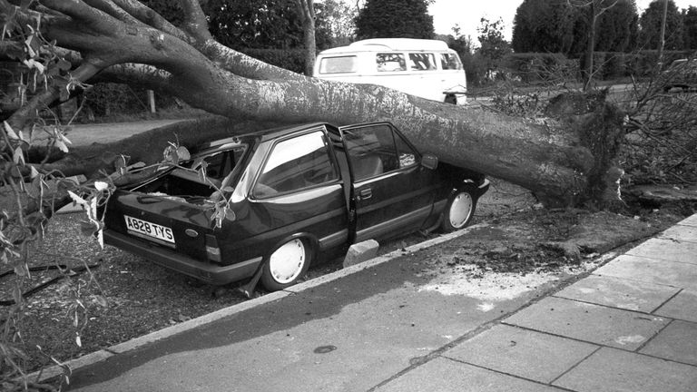 A car stands crushed by a falling tree after a hurricane hit Britain.
