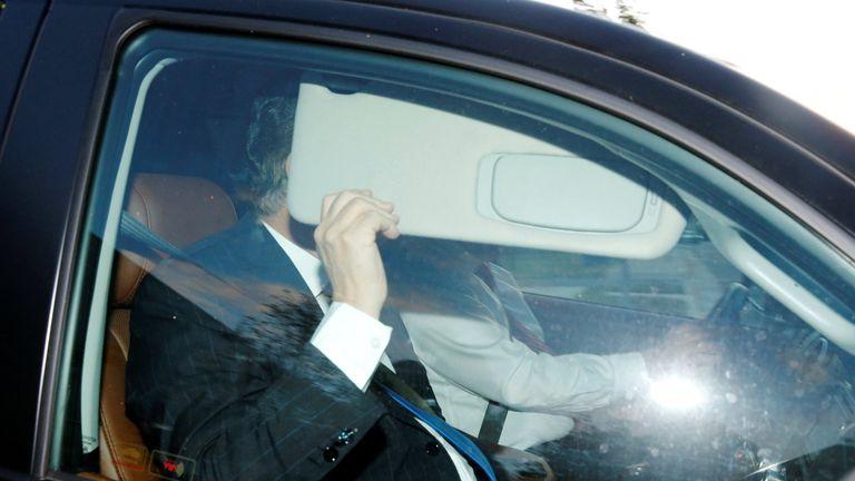 Paul Manafort hides behind his car visor as he leaves his home in Alexandria