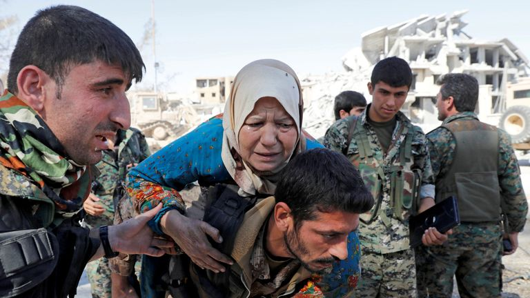 SDF fighters evacuate a civilian from the stadium after Raqqa was liberated from the Islamic State militants