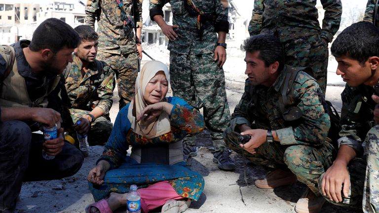 A woman cries after she was rescued by fighters of Syrian Democratic Forces at the stadium