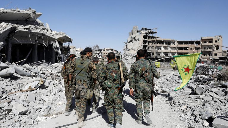 Fighters of Syrian Democratic Forces walk past the ruins of destroyed buildings near the National Hospital after Raqqa was liberated from the Islamic State militants