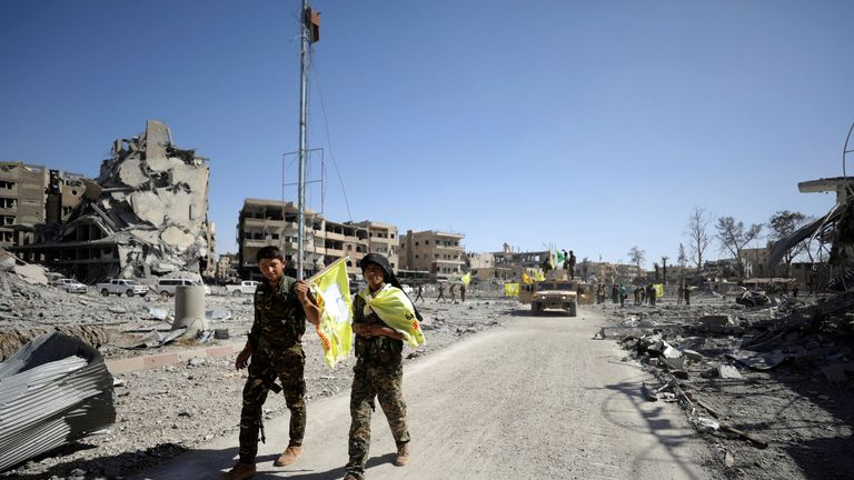 Fighters of Syrian Democratic Forces walk along a street in Raqqa