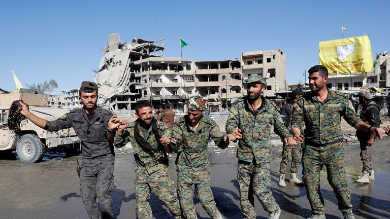 Fighters of Syrian Democratic Forces dance along a street in Raqqa