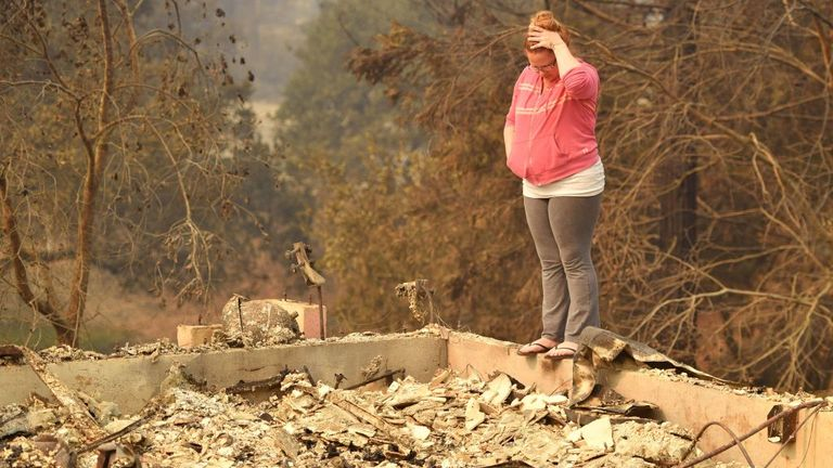 April Lee looks at the remains of a burned out home in Santa Rosa