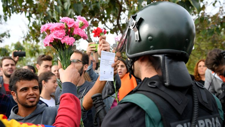 A man holds a bunch of carnations in front of Spanish officers in San Julia de Ramis