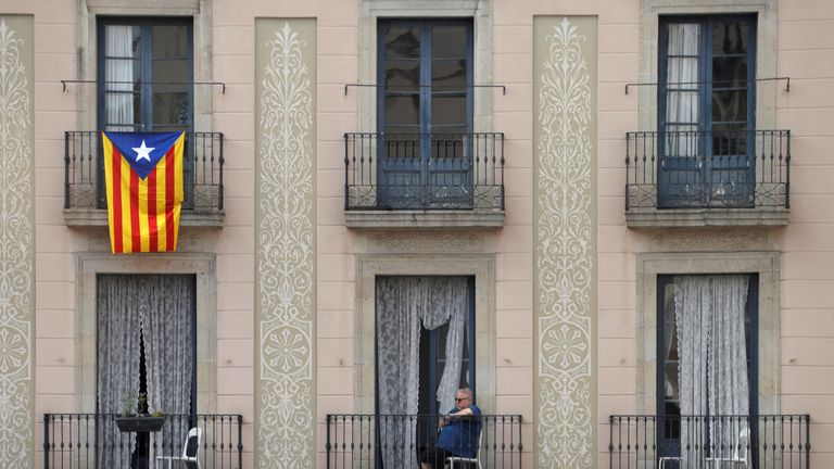 A Catalan flag hangs from a balcony as a woman watches a demonstration in a square in Barcelona