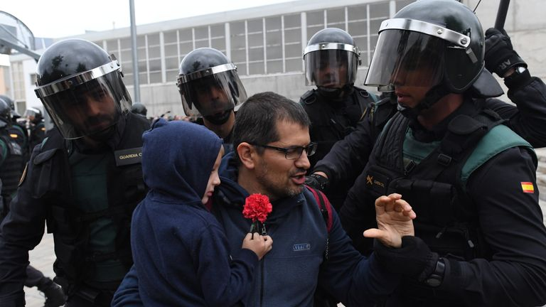 Police take hold of a man and a child holding a red flower