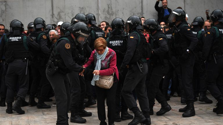 A elderly woman is helped as police move in on the crowds