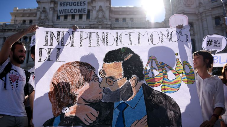 Protesters hold a placard depecting Spanish Prime Minister Mariano Rajoy kissing kissing Catalan president Carles Puigdemont during a demonstration called by the 'Let's talk' (Parlem,Hablemos) association for dialogue in Catalonia in October 07, 2017 at Cibeles square in Madrid. Spain braced for more protests despite tentative signs that the sides may be seeking to defuse the crisis after Madrid offered a first apology to Catalans injured by police during their outlawed independence vote.