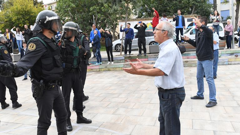 n elderly man confronts an officer as police move in on the crowds