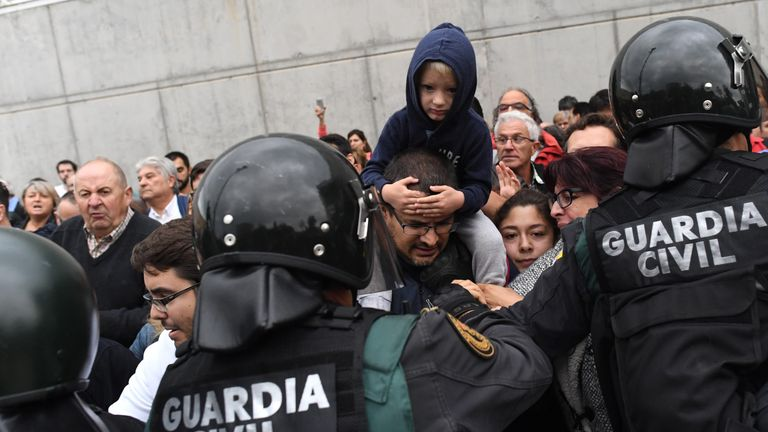 A child sits on the shoulders of a person as police move in on the crowds